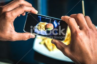 Taking a picture of an hamburger with french fries Royalty Free Stock Photo. Get superb discounts on images, illustrations, Videos and music clips at iStockphoto with Coupons.