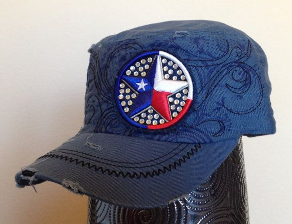 This distressed blue cadet cap features a navy blue screen printed pattern across the front of the hat, along with black embroidery that follows the pattern. There is a Texas star embroidered with red, white and blue thread and embellished with silver rhinestones on the front left of the hat and there are pieces distressed/torn over the hat and bill for a fun 'worn' look.  - Three-panel construction. - Embroidered design. - Screen printed design. - Silver rhinestones.
