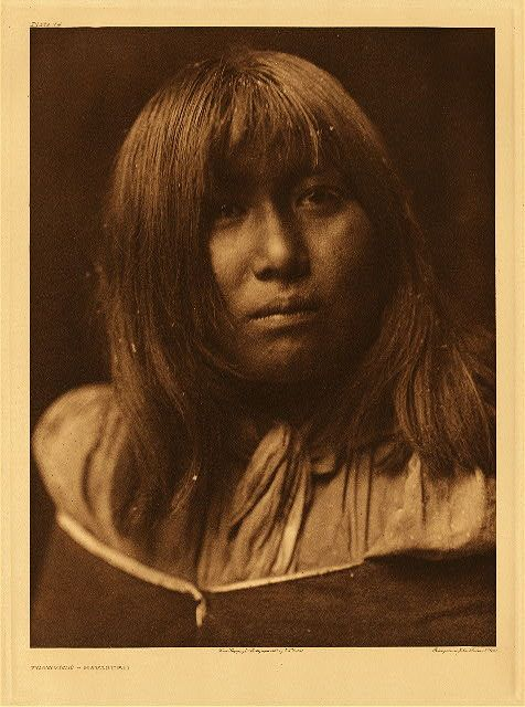 """Tonovige - Havasupai, 1907. Photogravure. Curtis Caption: """"This portrait was made in winter while a party of Havasupai were encamped in the high country above their cañon home. As a snowstorm was raging at the time, the woman's hair became dotted with flakes, as the picture reveals."""""""
