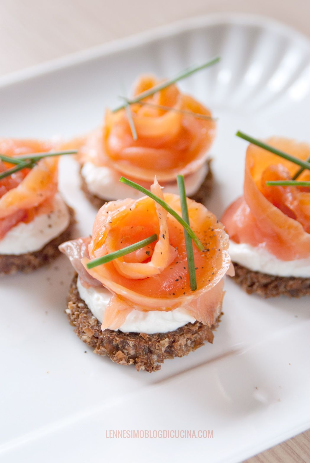 Roselline di salmone, appoggiate su dischetti di pane nero e arricchite da yogurt greco, sono ideali per aprire un pranzo di festa o una cena speciale (salmon roses) recipe & photos ©annafracassi