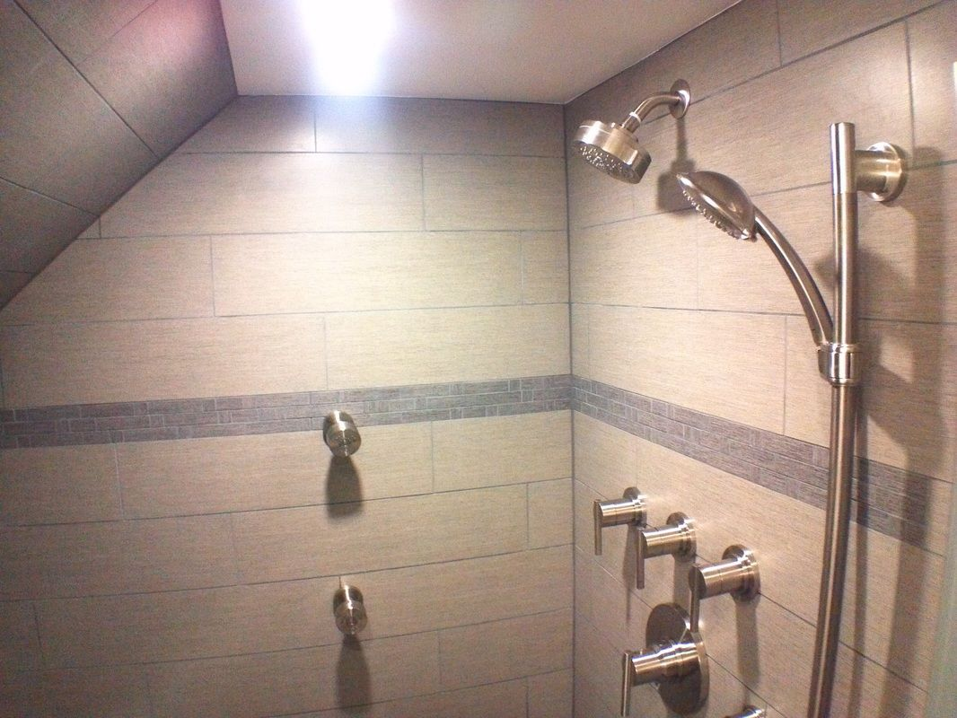 Shower with tile accent row and side body sprays for Basement bathroom tile ideas