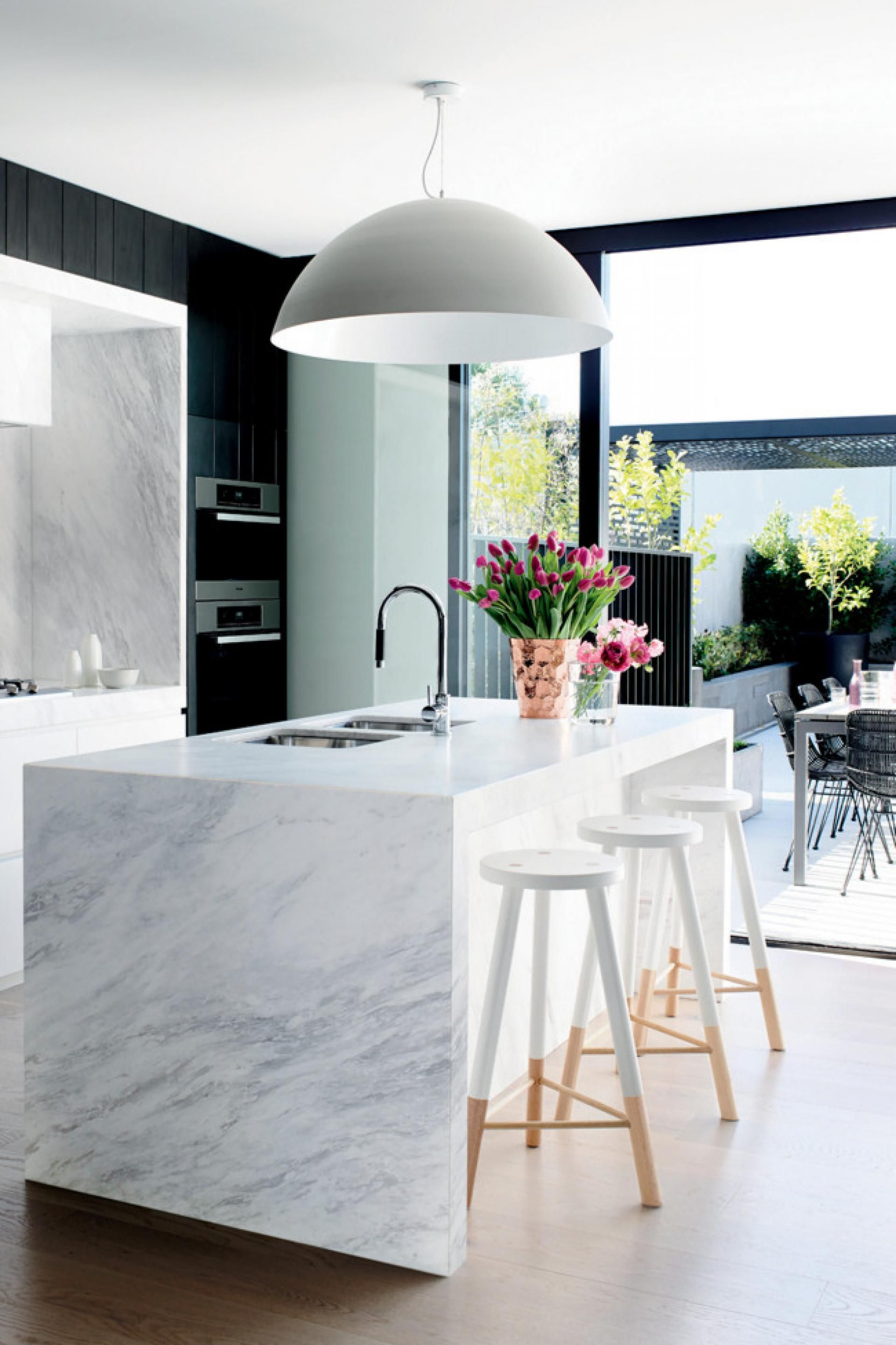 over sized pendant light over the kitchen island marble bench is in ...