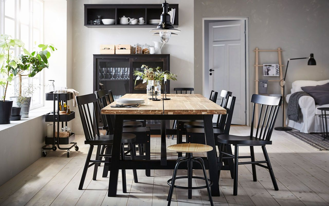 The acacia skogsta dining table is positioned in the centre of a beige and black dining room surrounded by a mix of black chairs