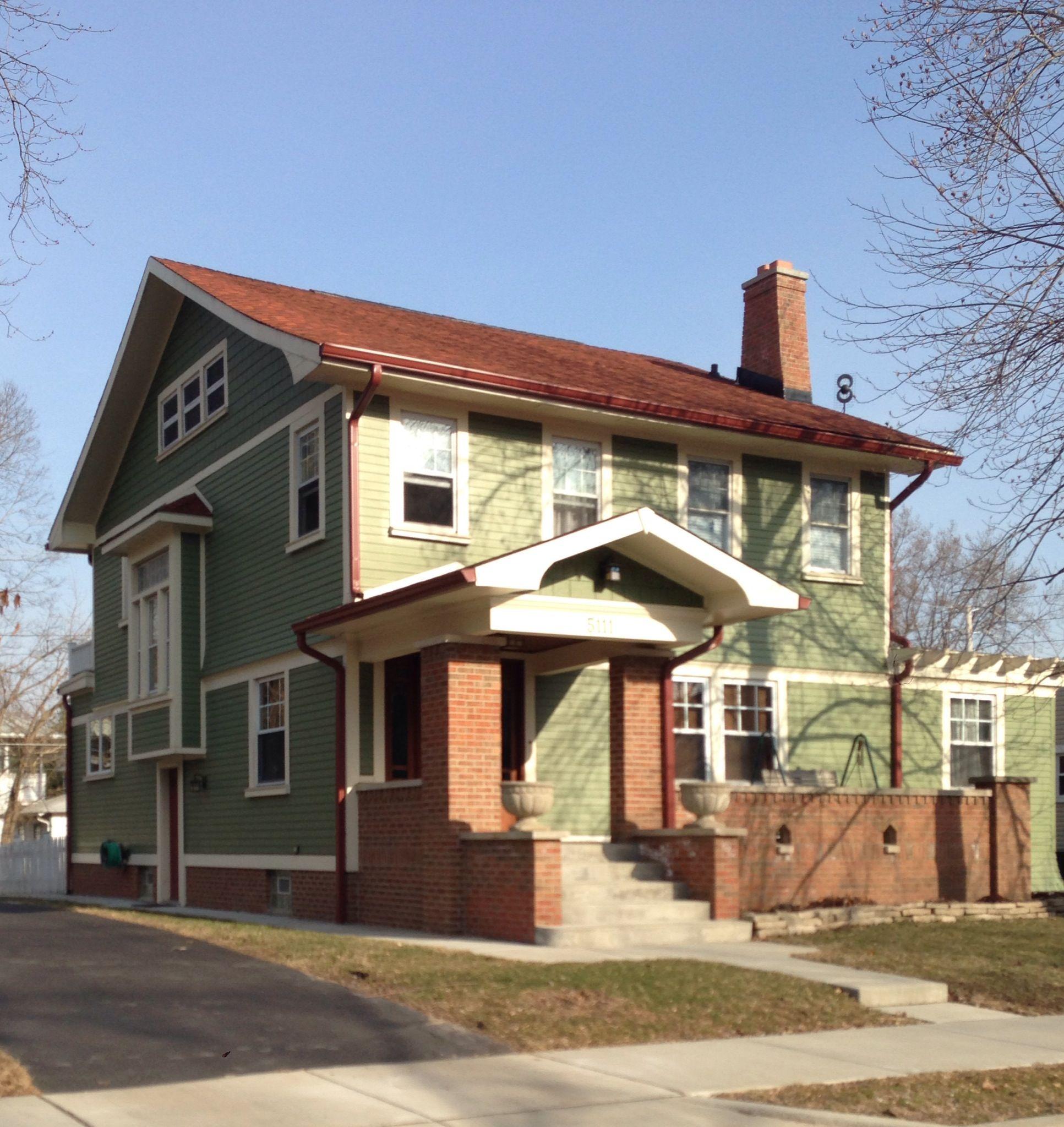 Brick porch. Cream trim. Green house.