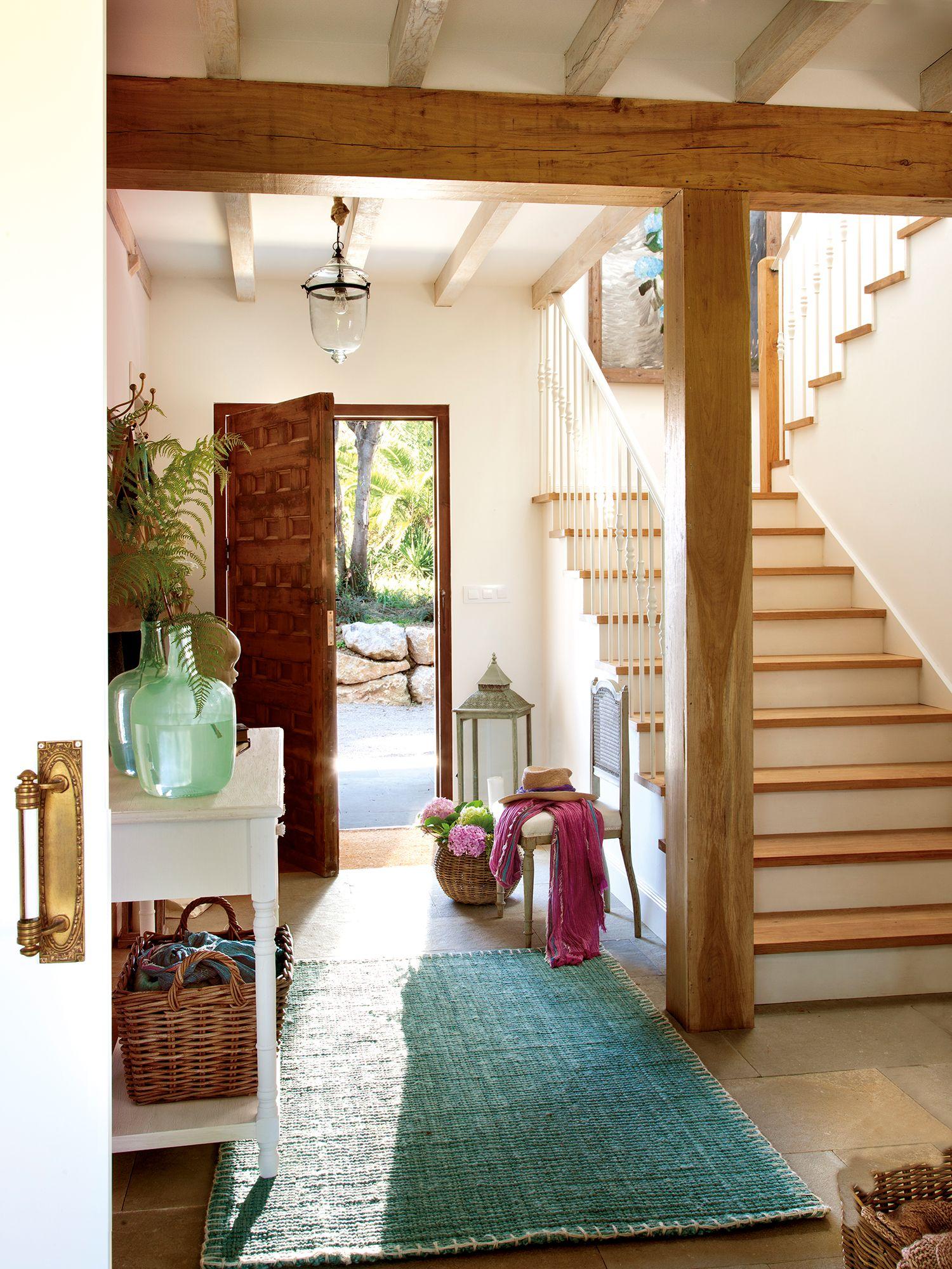 Recibidor de casa de pueblo con escalera vigas de madera - Decorar una entrada estrecha ...