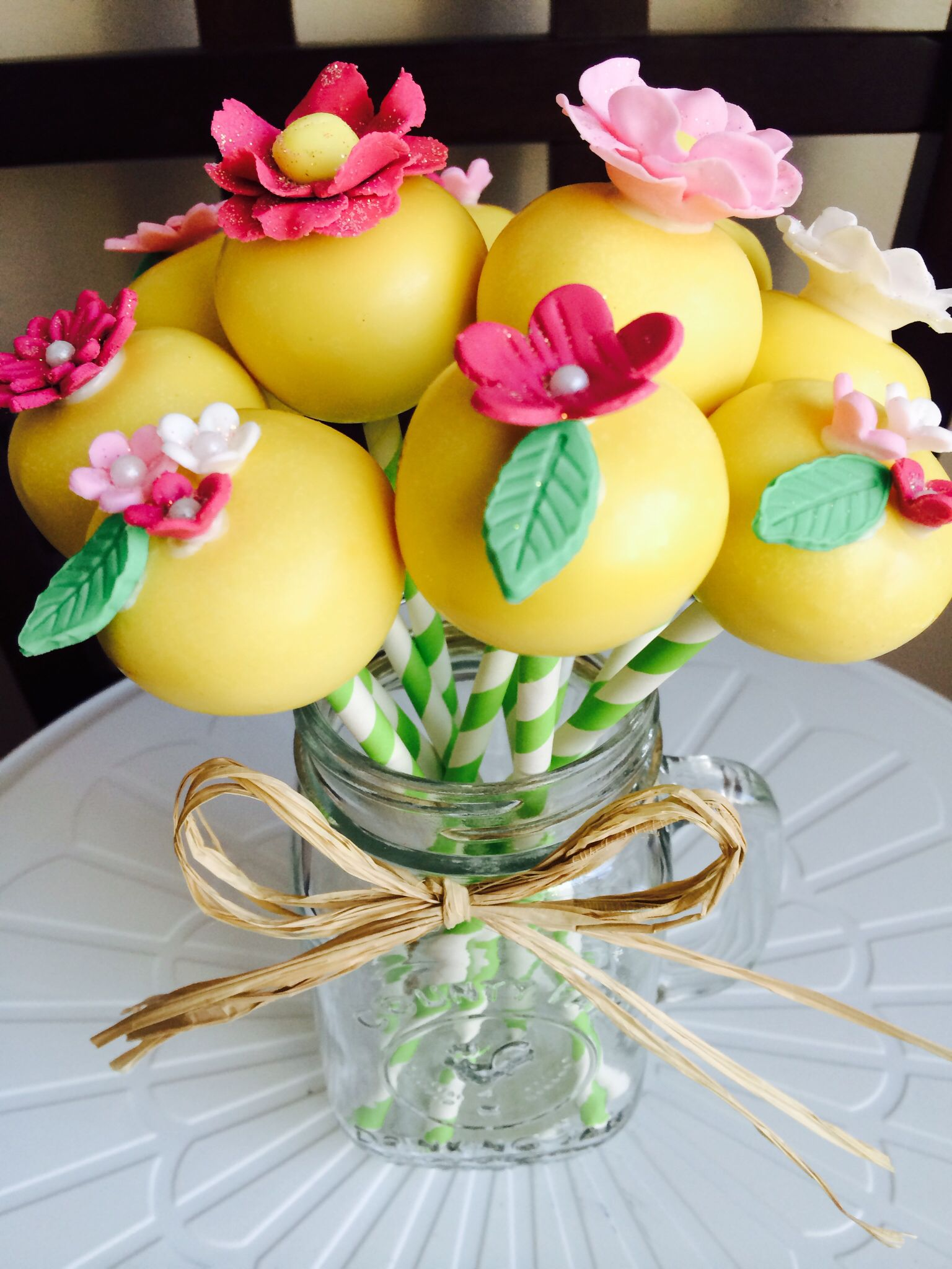 Yellow cake pops with vibrant colored flowers! Mason jar mug used as a vase!