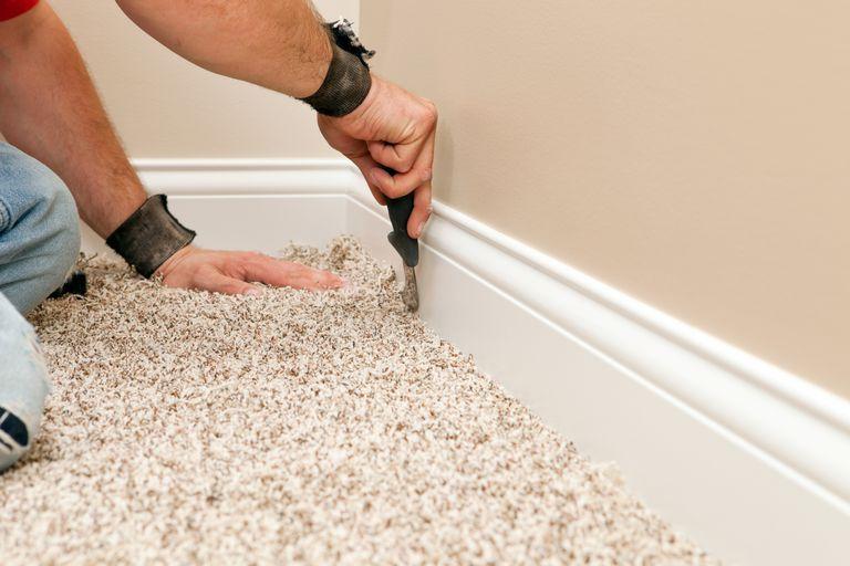 A Man Tucking Carpet Underneath White Baseboard