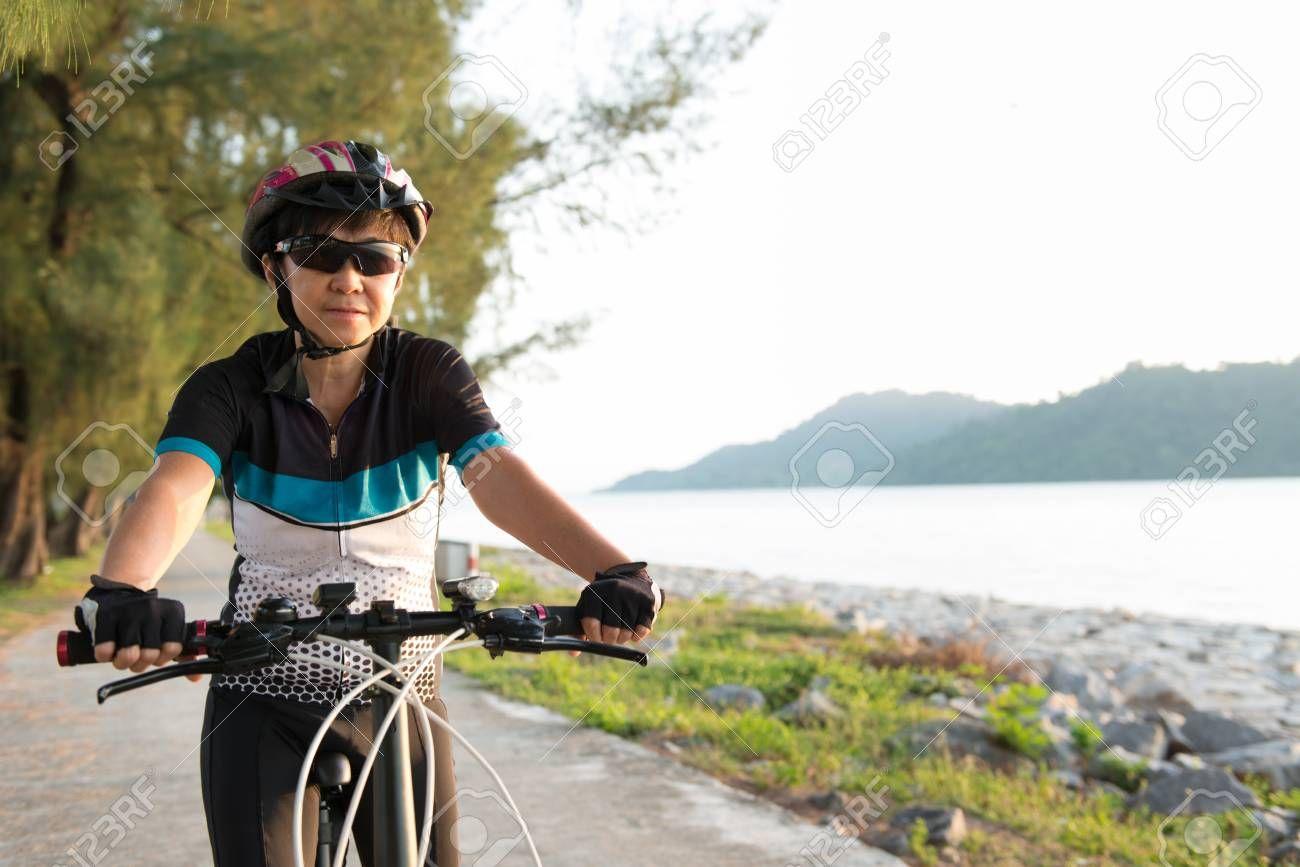 Joyful senior Asian woman riding a bicycle