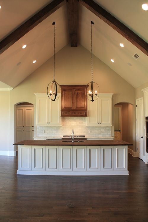 Vaulted ceiling wood counter top island in kitchen for Pendant lighting for high ceilings