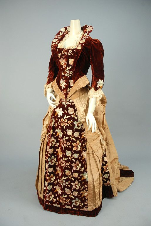 """Boned garnet velvet bodice having wired collar and self buttons, polychrome embroidered floral and lace trim, trained bustle skirt of tan moire silk with embroidered velvet front panel and lace swags. Petersham label """"Mme. Dellac, New York"""". B-36, W-26, skirt L-42-58. (Lace bodice trim torn) very good. MMA. $3,120"""