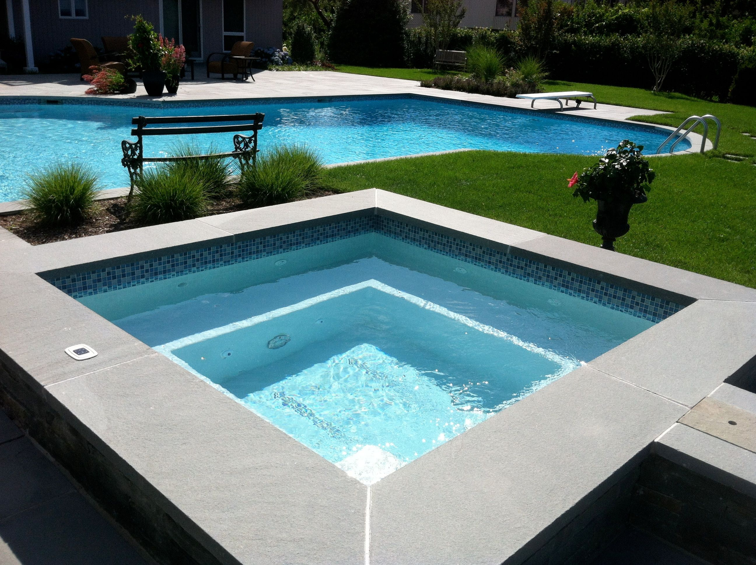 Stand alone gunite spa and fee form pool with glass tile and