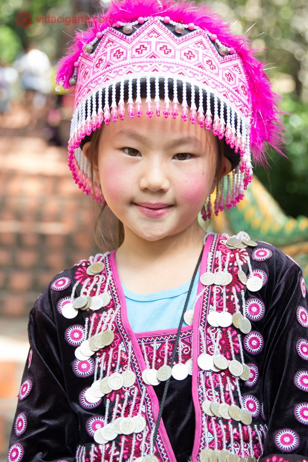 Menina tailandesa posa em frente a escadaria em formato de dragão que dá acesso ao Wat Doi Suthep, em Chiang Mai, na Tailândia. Veste roupas e chapéu em tons de rosa e preto com pingentes estampas em motivos tradicionais.