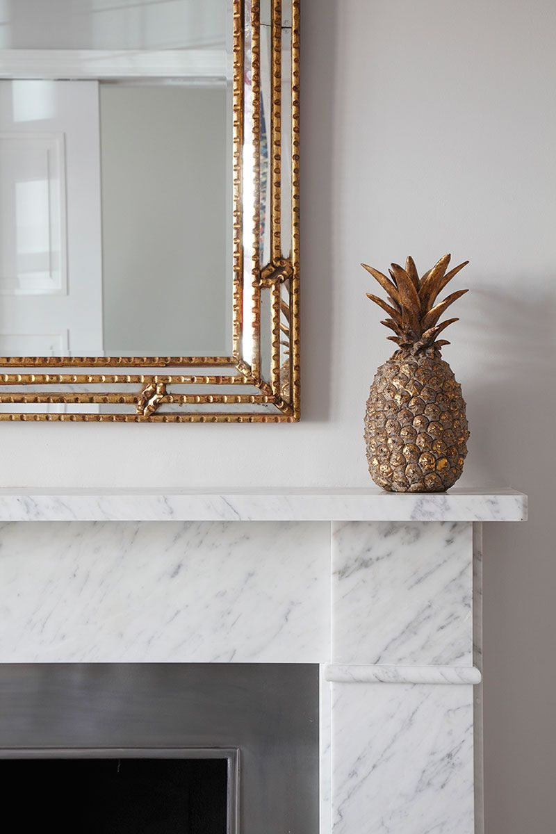 Brass mirror and pineapple on simple marble chimneypiece itus all
