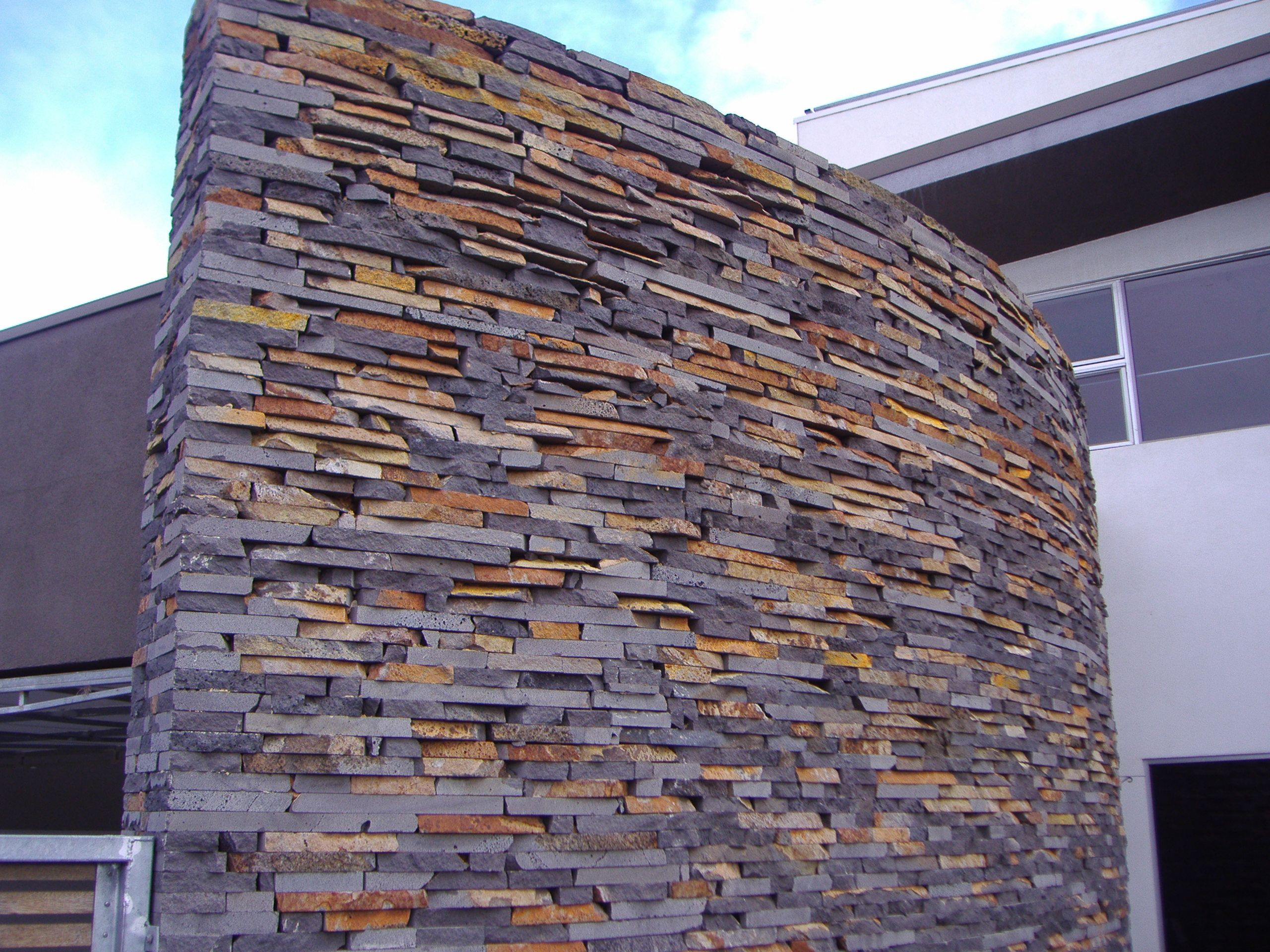 Rustic bluestone stackedstone along a curved wall on the for Curved wall