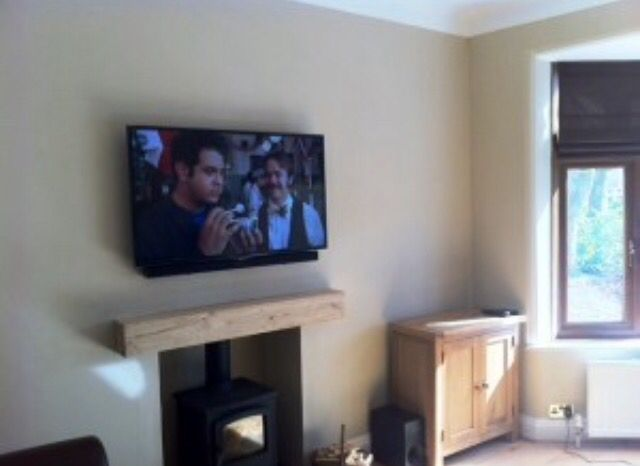 Smart Flat Screen Tv Above A Wood Burning Stove With Oak Wood