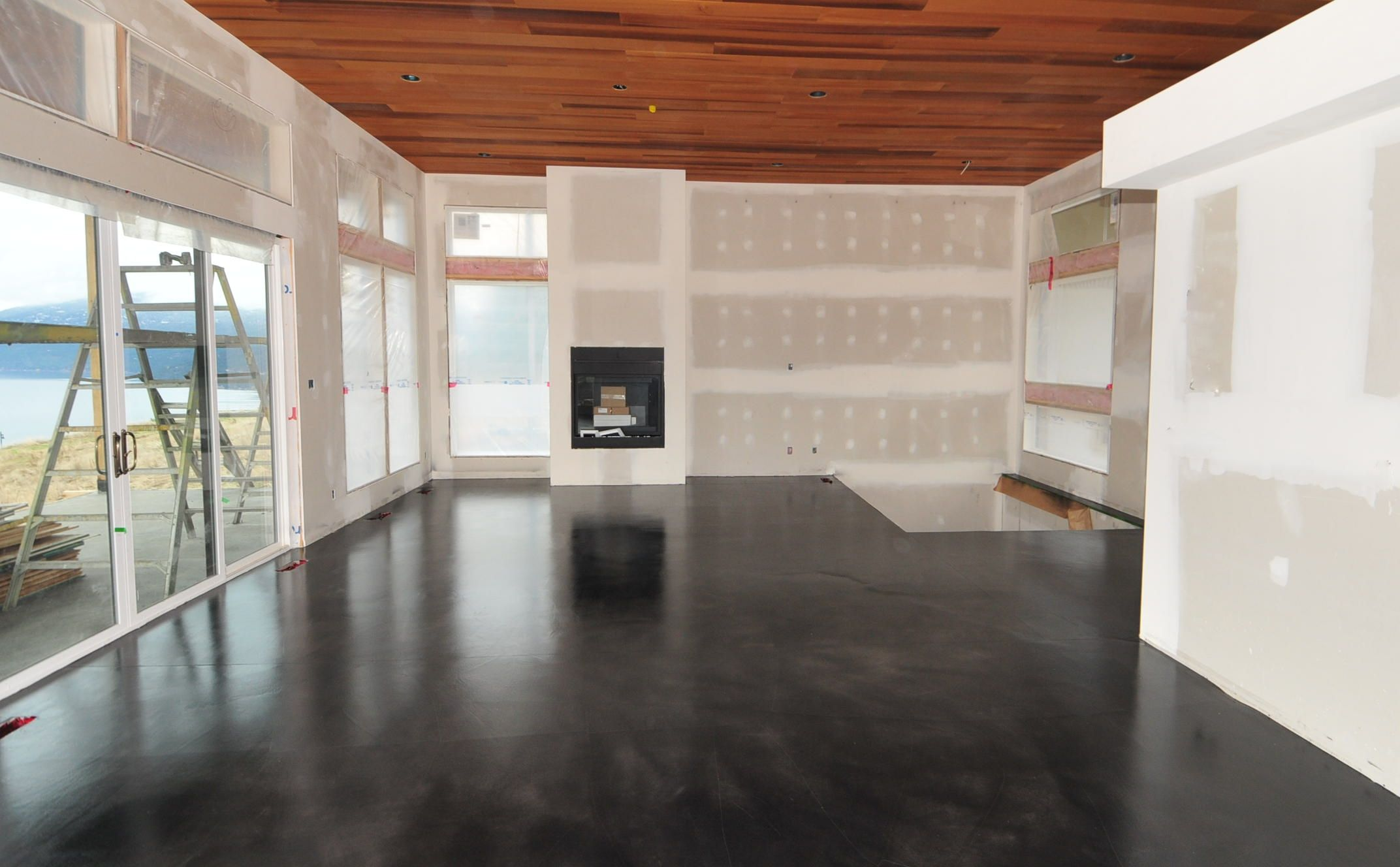 A modern black stained concrete floor, created by MODE CONCRETE in Kelowna  BC.