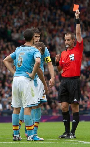 Spain's Inigo Martinez, left, is shown the red card by referee Mark Geiger, right,  during the group D men's soccer match between Japan and Spain at the London 2012 Summer Olympics, Thursday, July 26, 2012, at Hampden Park Stadium in Glasgow, Scotland. Photo: Chris Clark / AP