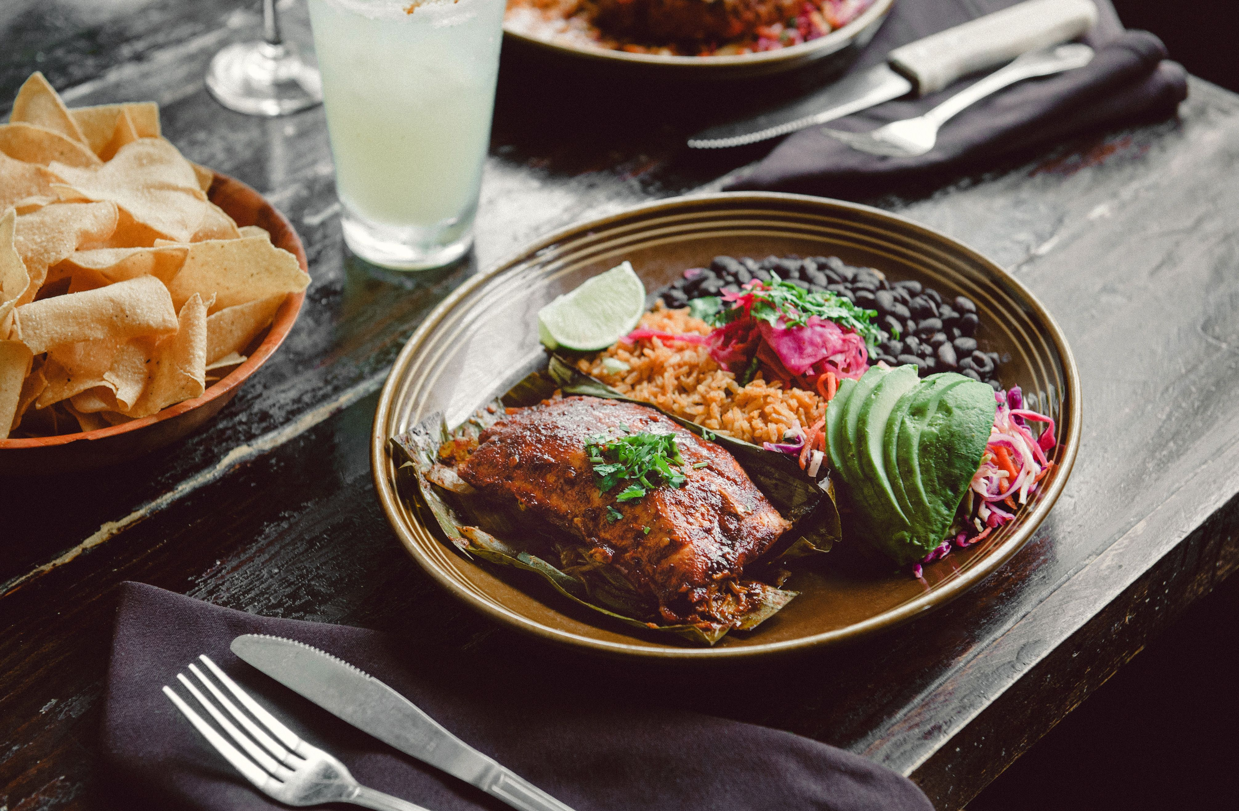 Salmon filet -- slow-cooked with pasilla peppers and onions, then baked in a banana leaf and topped with a tequila-ancho glaze. Served with traditional Mexican rice, black beans and sliced avocado.