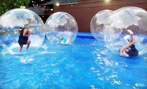 Staff members supervise customers as they float atop pools of water in inflatable spheres