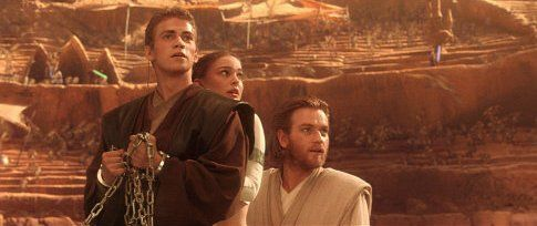Just as their fate seems sealed, Anakin Skywalker (actor Hayden Christensen), Padmé Amidala (actress Natalie Portman), and Obi-Wan-Kenobi (actor Ewan McGregor) look up to see the Geonosis arena filled with Jedi rescuers.