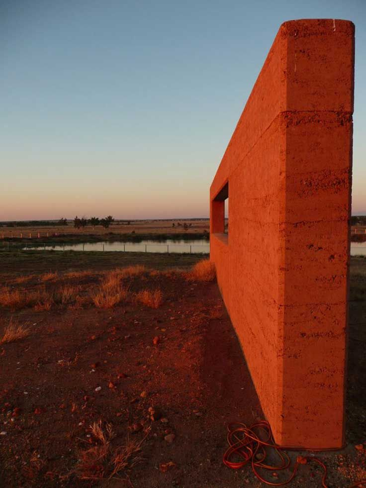 Rammed earth wall colours are dramatically highlighted in the sunset in this Station homestead in far western Queensland, Australia.
