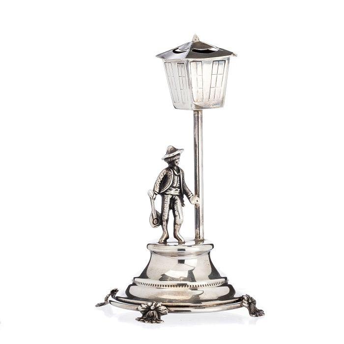 Paliteiro 'fadista' em Prata portuguesa, contraste águia (pós 1985), representando figura masculina de fadista e lampão sobre base redonda com pés. Peso aprox.:124grs. Dim.:15,5cm.