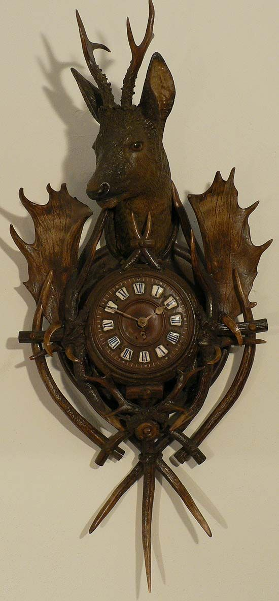 A Black Forest Antler Wall Clock With Carved Deer On Top