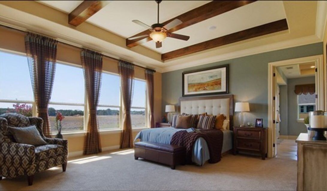 master suite with tray ceiling and wooden beams  guest