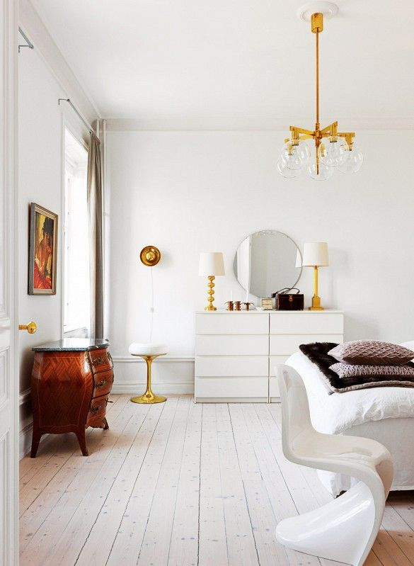 Create an elegant bedroom with white wood flooring and gold fixtures, like this bubble-like chandelier