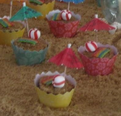 Chocolate cupcakes, brown sugar on top of buttercream, Airheads sour strip candy as towels, mint candies as beach balls