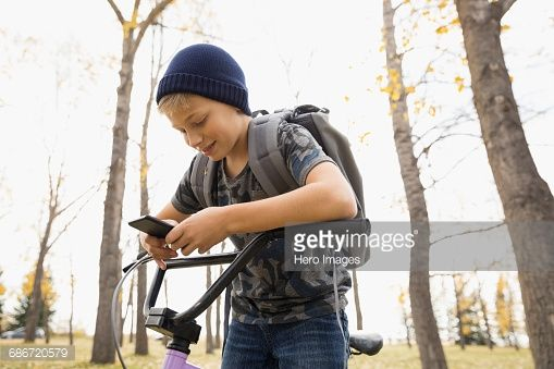 Stock Photo : Tween boy with bicycle texting with cell phone in autumn park