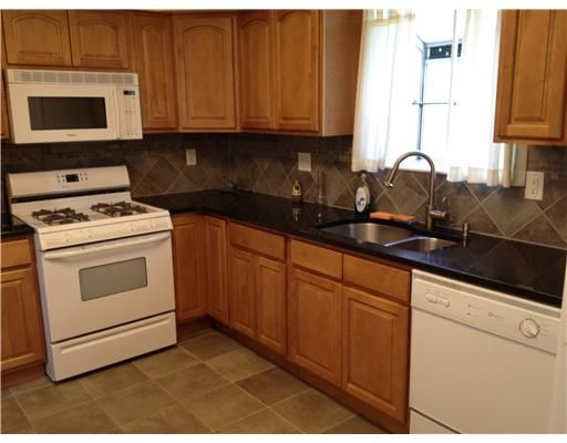 bright kitchen with oak cabinets, black granite counters, tile