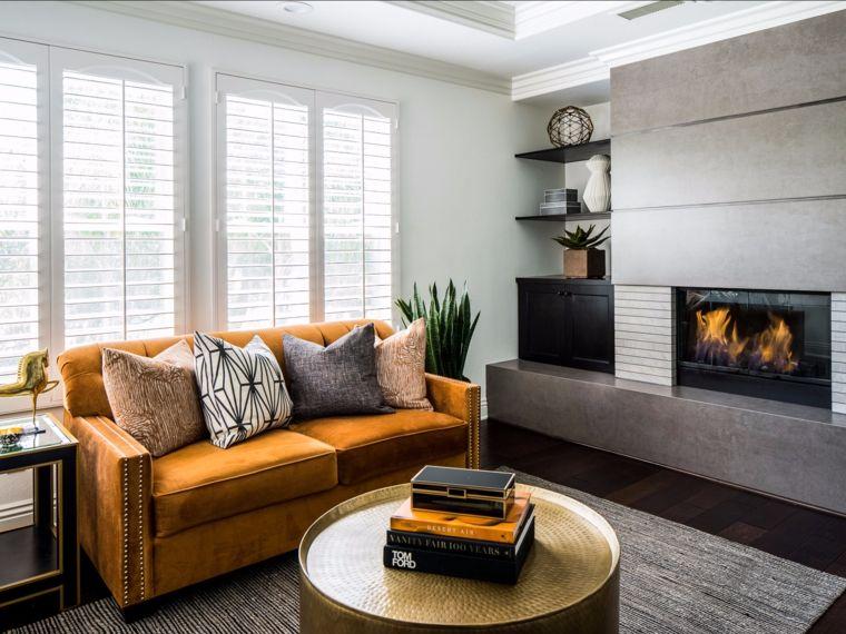 Soggiorno con un divano color senape pavimento in legno scuro