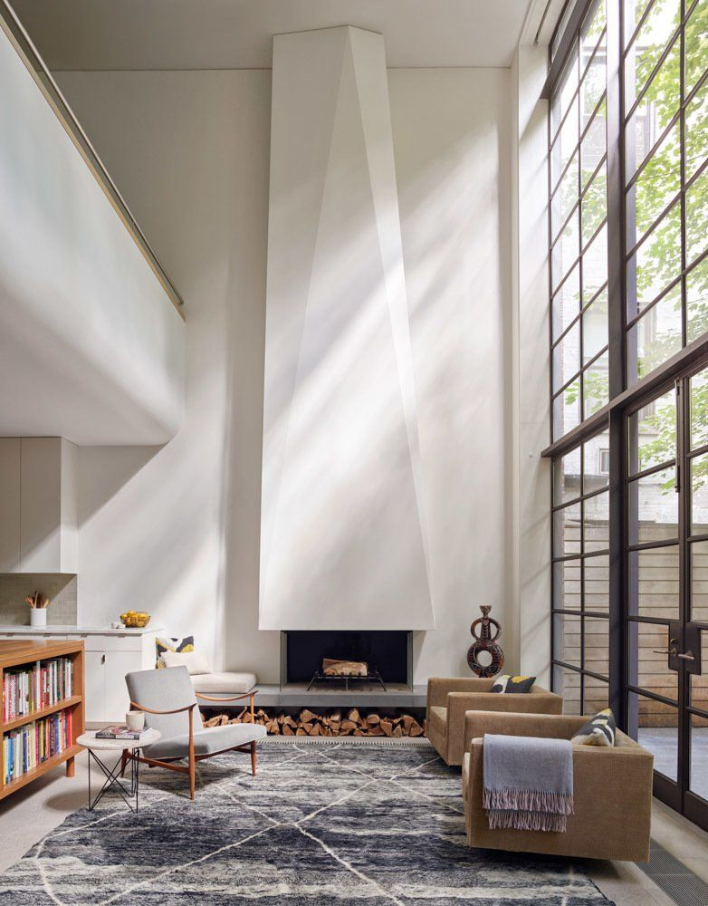 this sculptural and asymmetrical fireplace anchors the. Black Bedroom Furniture Sets. Home Design Ideas