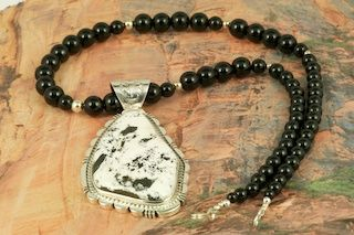 Genuine White Buffalo Turquoise set in Sterling Silver Pendant on a Genuine Black Onyx Necklace with Sterling Silver Beads and Clasp. This Beautiful Stone is formed from the minerals Calcite and Iron. It is mined near Tonopah Nevada. Created by Navajo Artist Freddy Charley. Signed by the artist.