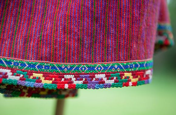 The hems are decorated with both crochet and woven ribbons. The skirts are made of striped home woven wool.