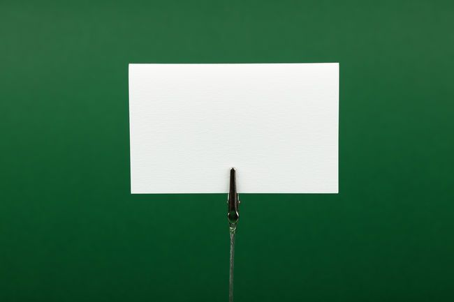 white paper sign over colorful green background blank business