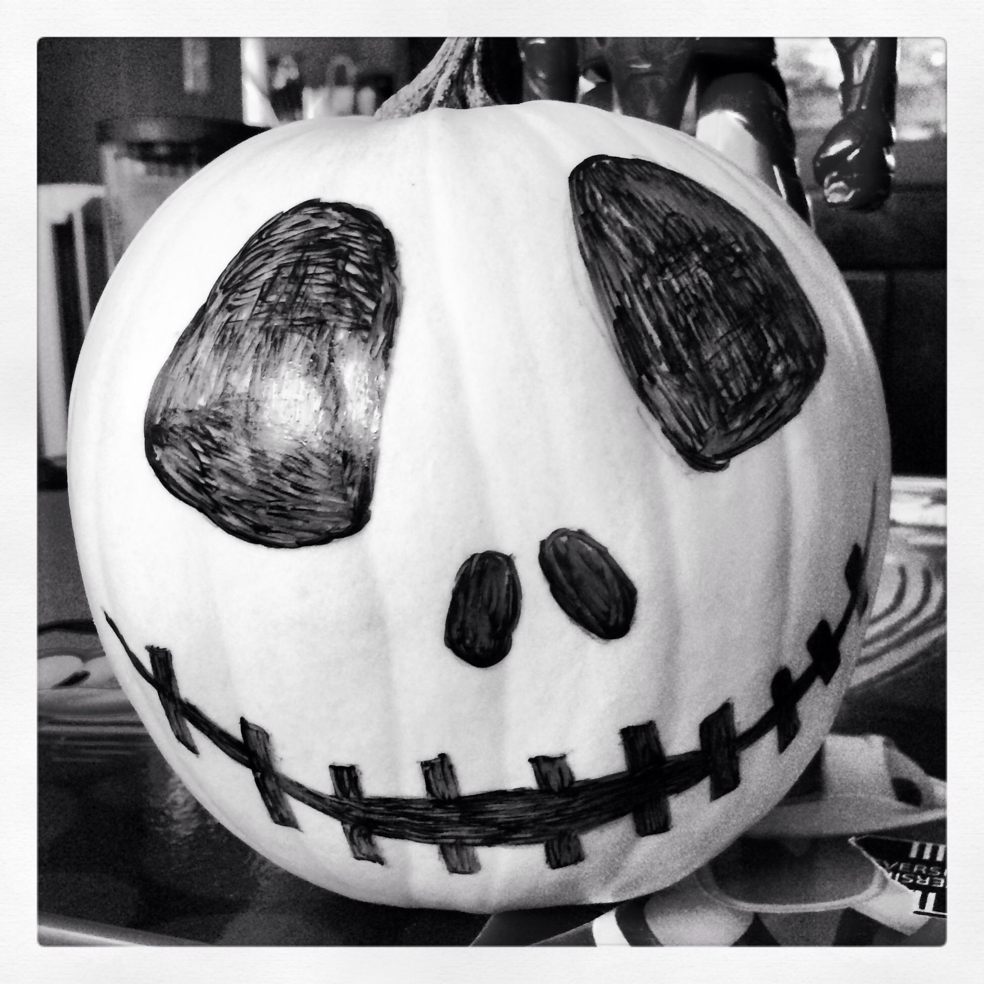 White pumpkin with a jack skellington face drawn on (With