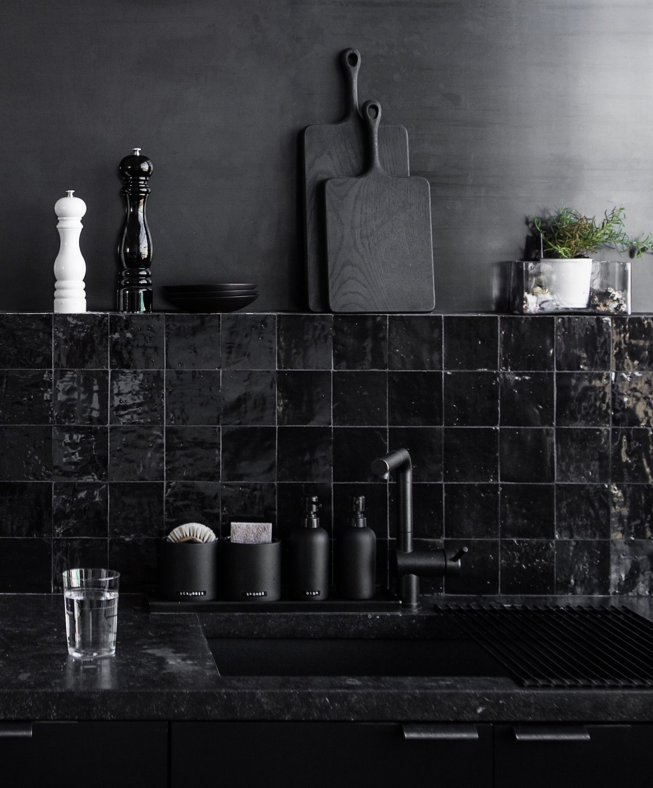 """The kitchen has two handmade backsplashes: a row of hand-glazed, glossy black Moroccan Clé tile, and a """"bleached metal"""" steel wall surround—an effect Hollis developed with Oakland's Chris French Metal """"to add depth, interest, and contrast to the space,"""" she says."""