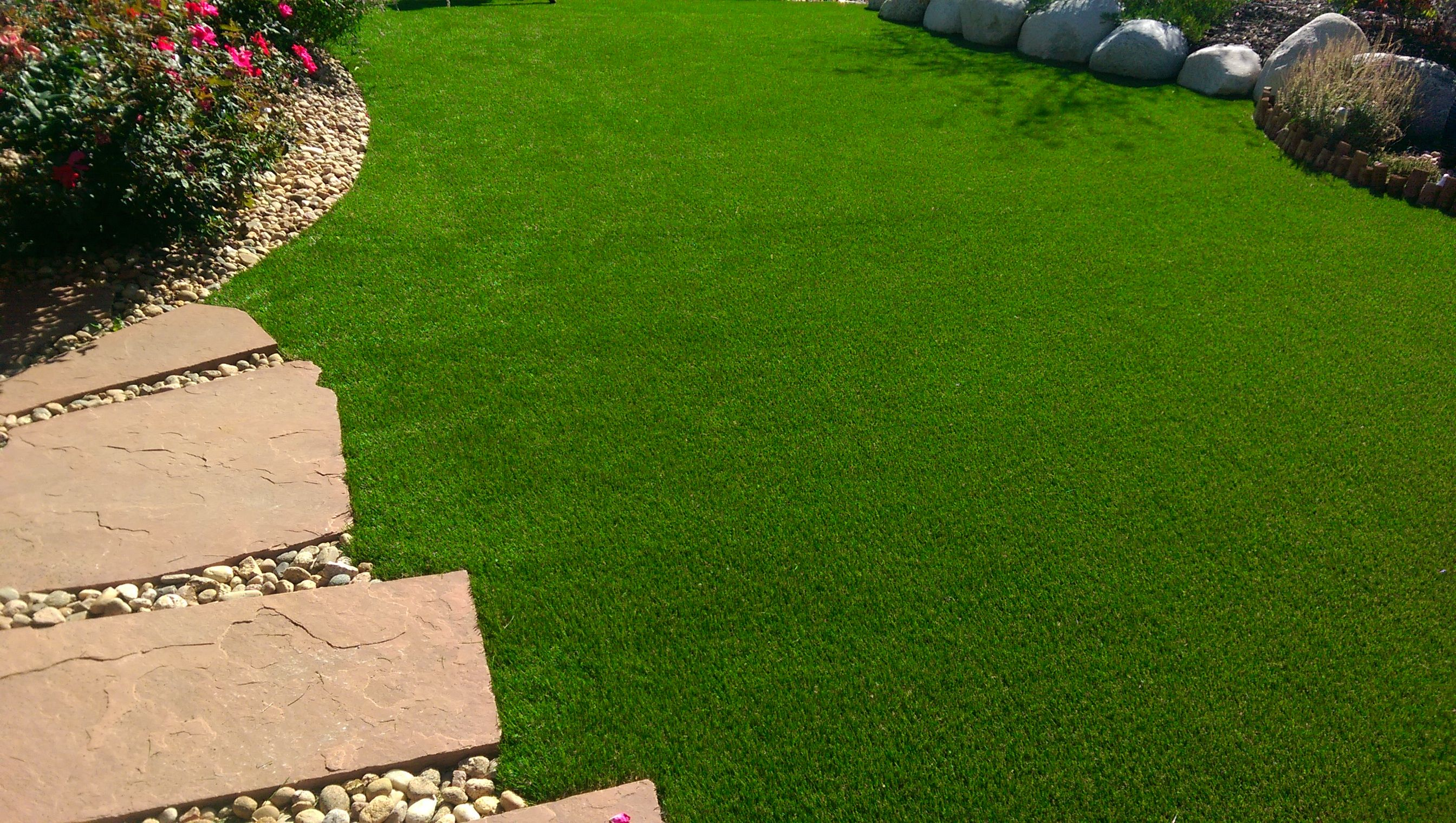 Artificial turf pros and cons - Artificial Turf Lawn With Rock And Flagstone Borders