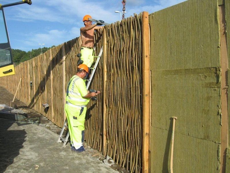 Installation in progress of a woven willow noise barrier # ...