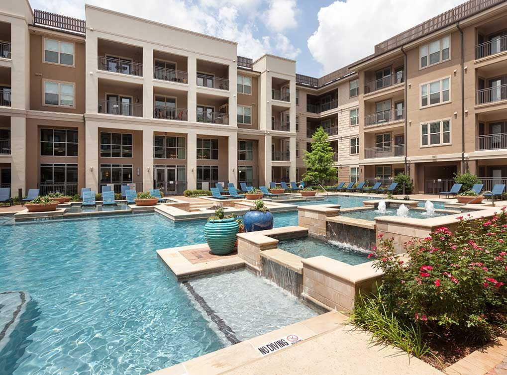 Resort Style Swimming Pool With Tanning Island And Elaborate Water Features At Amli On Maple Luxury Apartments Community Pool Resort Style Apartment Building
