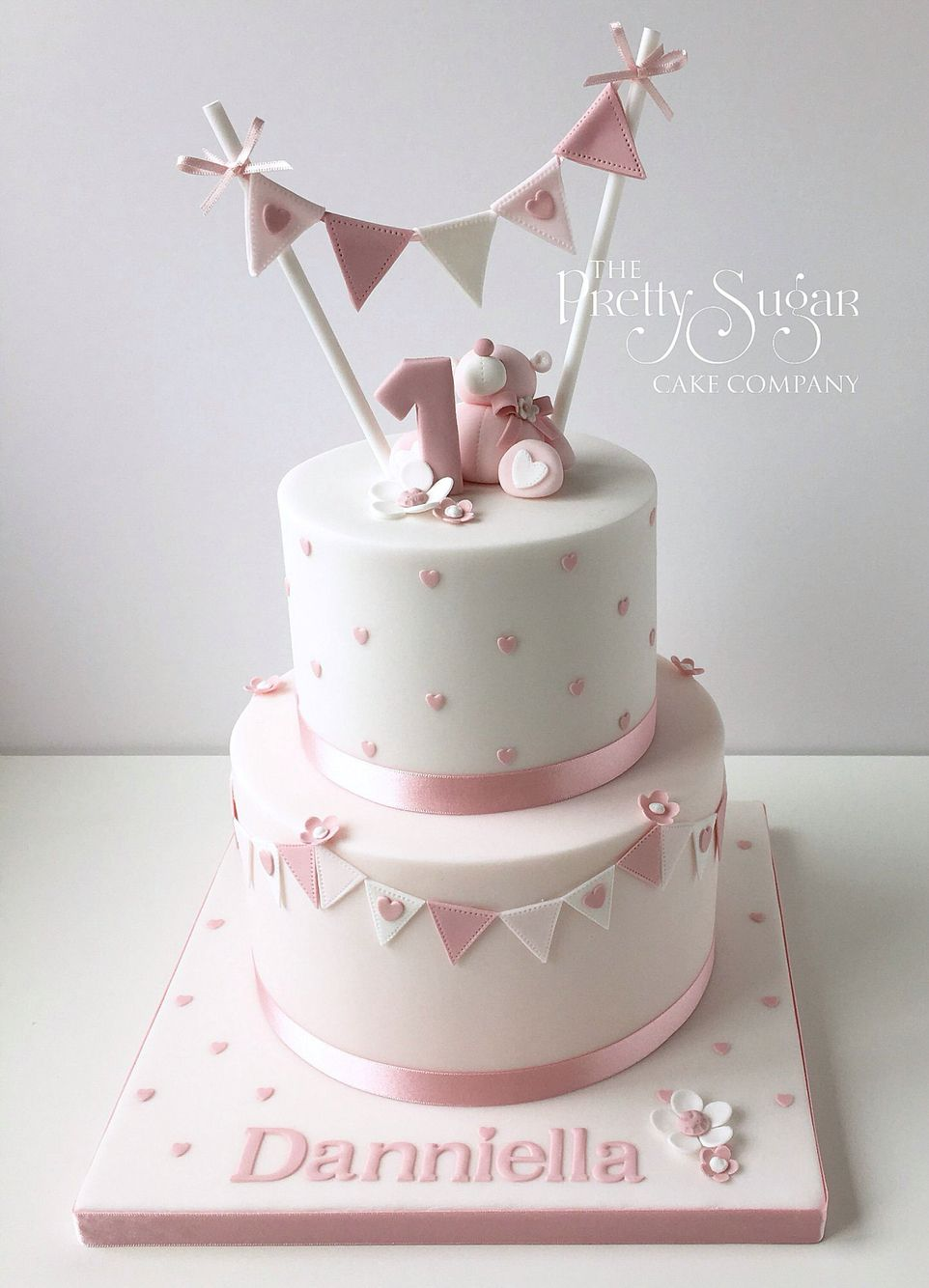 Pink polka dot first birthday cake with teddy & bunting