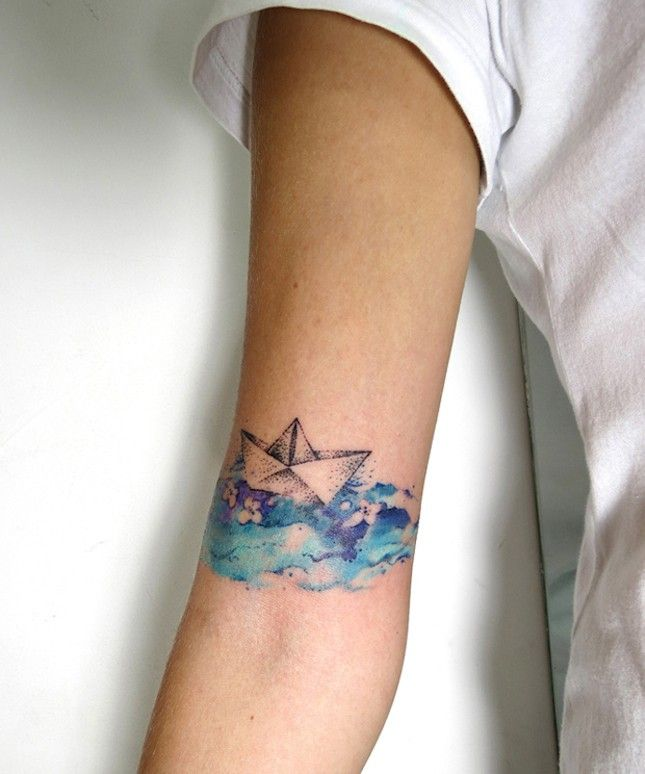 581cf6aed25ae The combo of watercolor waves + an origami boat make this whimsical tattoo  so swoon-worthy.