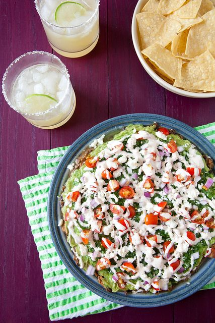 Modernized Mexican Seven Layer Dip with chorizo refried beans, tomatillo salsa, guacamole, queso fresco and chipotle lime sour cream. #cincodemayo #mexican #appetizers