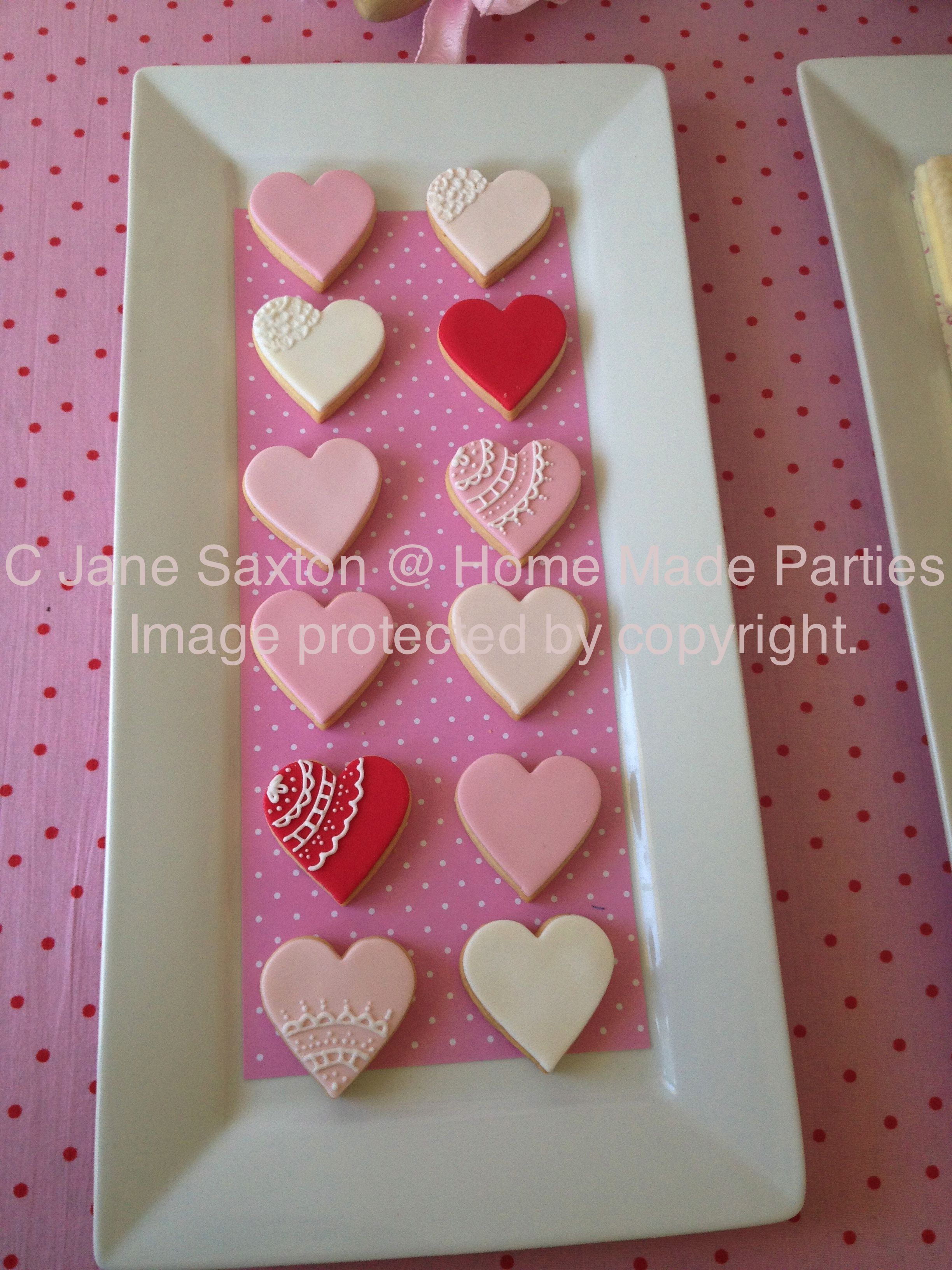 Pink and red ombre love heart cookies on love heart dessert table