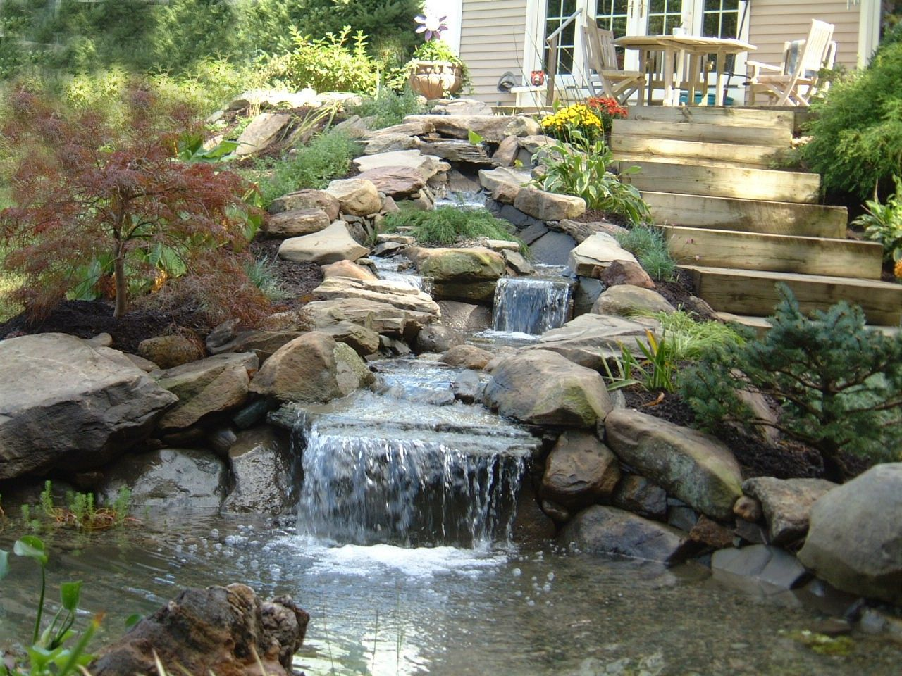 Gorgeous waterfall that trickles alongside deck pathway for Koi pond waterfall