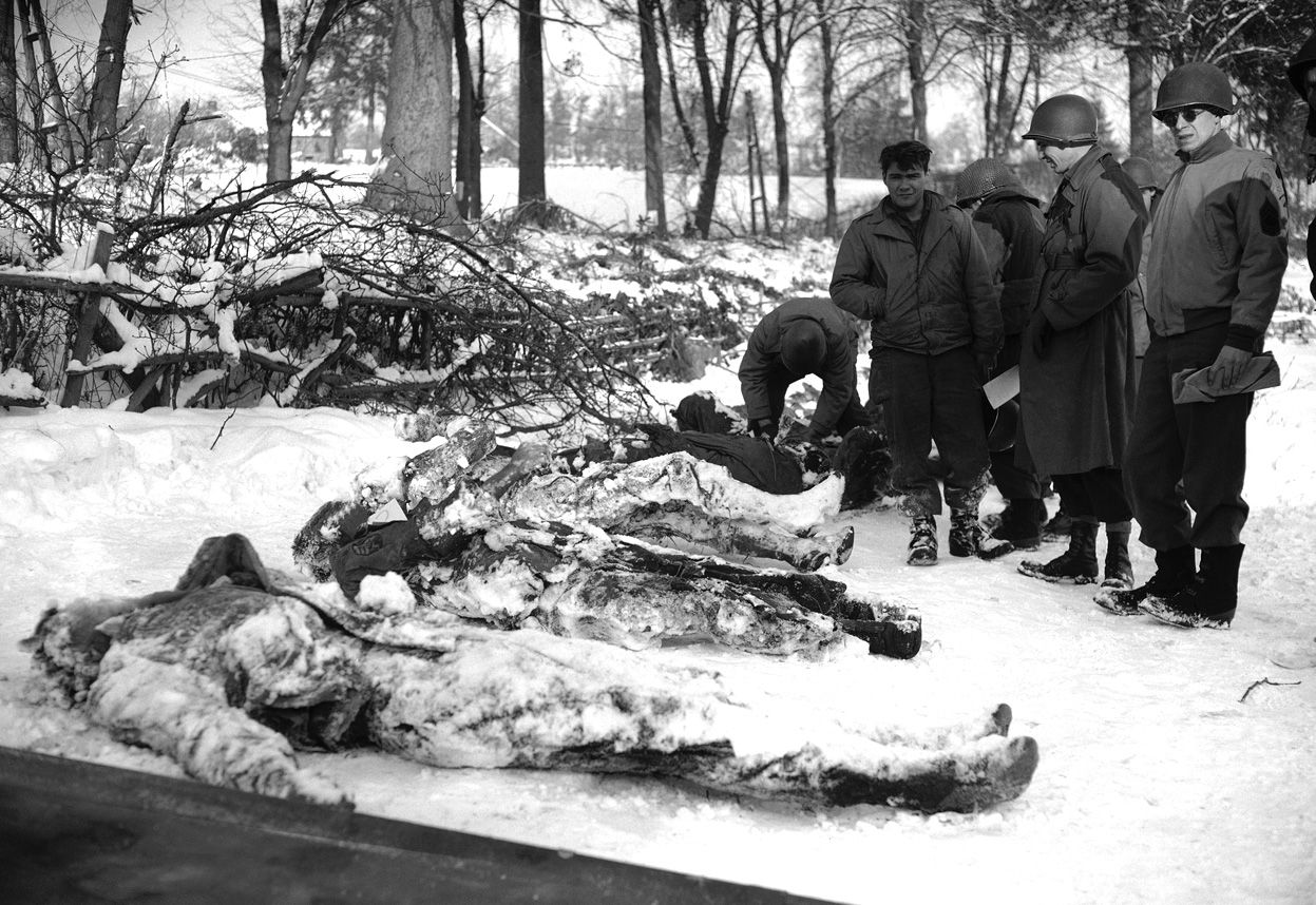 The bodies of some of the seven American soldiers that had been shot in the face by an SS trooper are recovered from the snow, searched for identification and carried away on stretcher for burial on January 25, 1945.