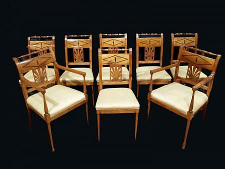 An elegant set of eight mid 19th century Biedermeier dining seats. The set with six chairs and two armchairs are in cherry and ebony. they are raised by circular front legs and square curved back legs. The turned arms below a straight square armrest ending with a circular design. The curved backs have a sunburst design below a diamond ebony inlay of an urn. Above is a turned carved top rail. All original patina.