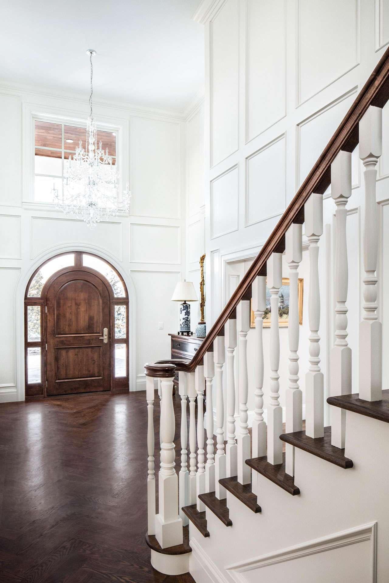 Stunning tall white entryway with an arched wood front door